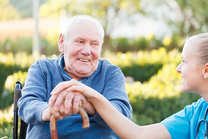 Elderly man smiling to young female doctor